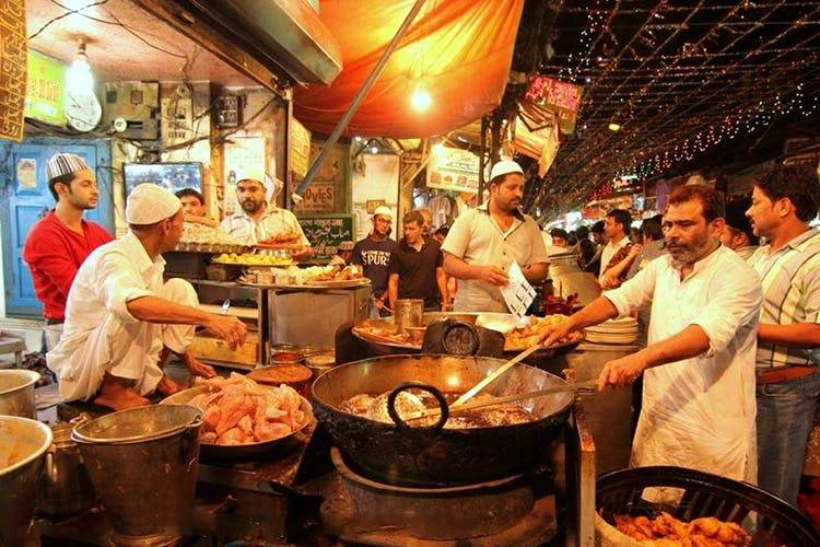 This is a picture of roadside eatery in Chandni Chowk. The shop is full of people, frying chicken and customers are in queue to buy and enjoy the delicacies