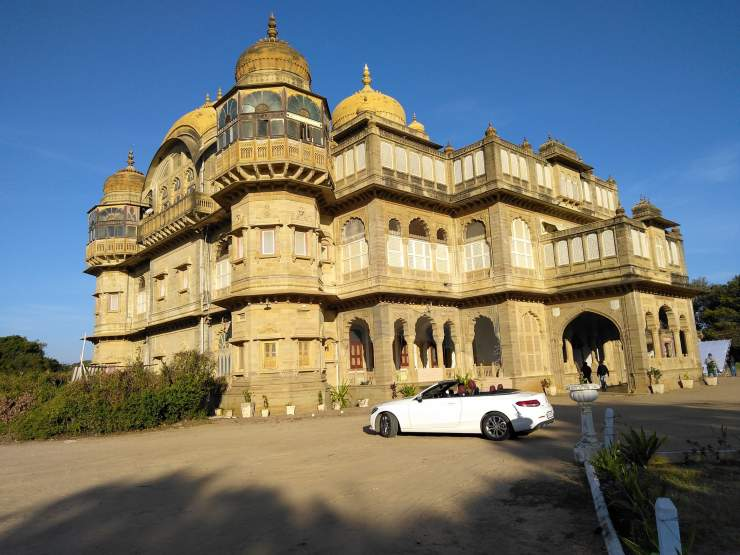 Look at the picture of a huge palace somewhere in Mandhavi. A white luxury car, just in front of the palace is adding beauty